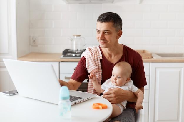 Binnenopname van een man met een bordeauxrood casual t-shirt met een handdoek op zijn schouder, die voor de baby zorgt en online vanuit huis werkt, glimlachend naar het notebookscherm.
