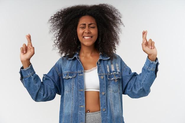Binnenopname van een positieve jonge, krullende, donkere dame die handen opsteekt met gekruiste vingers, een wens doet en de ogen gesloten houdt, geïsoleerd over een witte muur in vrijetijdskleding
