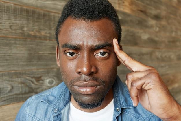 Binnenopname van een serieuze beu bebaarde afrikaanse man in een spijkerjasje die de vinger op zijn slaap houdt, fronsend en een boos gezicht heeft alsof hij zegt: gebruik je hersenen, stop met onzin te praten. lichaamstaal