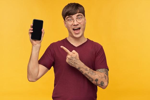 Binnenopname van een verbaasd, geschokt jong mannetje, draagt een rood t-shirt en wijst met een vinger naar een leeg zwart display van zijn telefoon