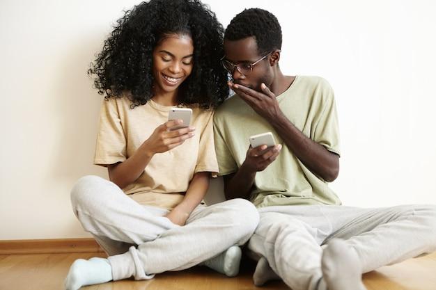 Binnenopname van een verbijsterde en geschokte jonge donkere man met een bril voor zijn mond terwijl hij naar het scherm van de mobiele telefoon van zijn vriendin keek.