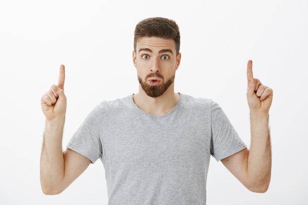 Binnenopname van geïnteresseerde en geïntrigeerde knappe mannelijke man met baard en bruin kapsel die lippen opvouwt van verbazing en nieuwsgierigheid, wijsvingers opheft die omhoog wijst en ondervraagd over grijze muur