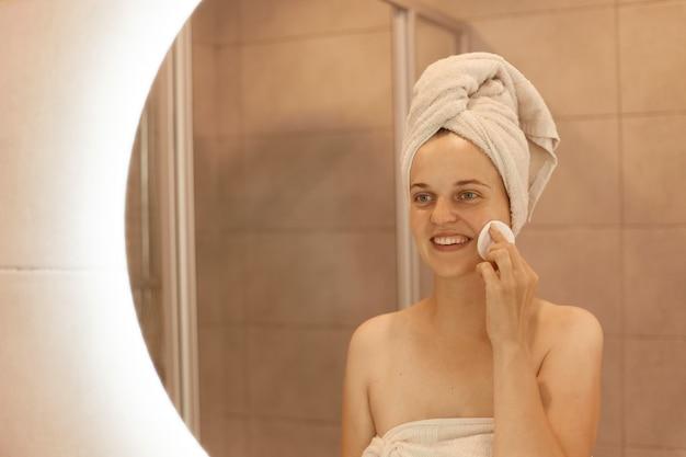 Binnenopname van gelukkige aantrekkelijke vrouwen die make-up in de badkamer verwijderen, wattenschijfje in handen houden en over haar wang wrijven, glimlachend kijkend naar haar spiegelbeeld in de spiegel.
