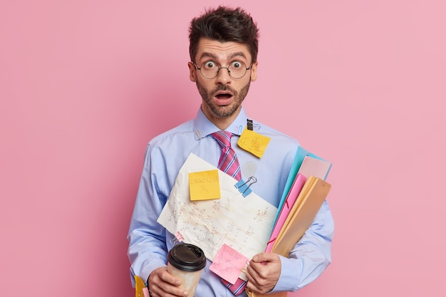 Binnenopname van geschokte bekwame mannelijke student staart met uitgestoken ogen en met open mond werkt aan een project of bereidt zich voor op examens, schrijft informatie op papieren om te onthouden dat hij koffie drinkt om mee te nemen