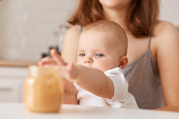 Binnenopname van gezichtsloze moeder die haar dochtertje met groentepuree voedt, charmante peuterbaby die hand uitrekt naar pot met eten, zich voedt.