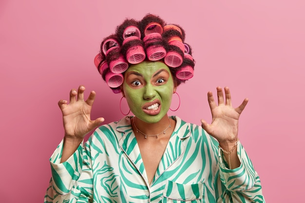 Binnenopname van huisvrouw maakt een boze grimas, heft handen op als poten, klemt tanden, draagt haarrollers, schoonheidsmasker voor verjonging, gekleed in huiselijke kleding. vrouwen, huidverzorging, cosmetologie.