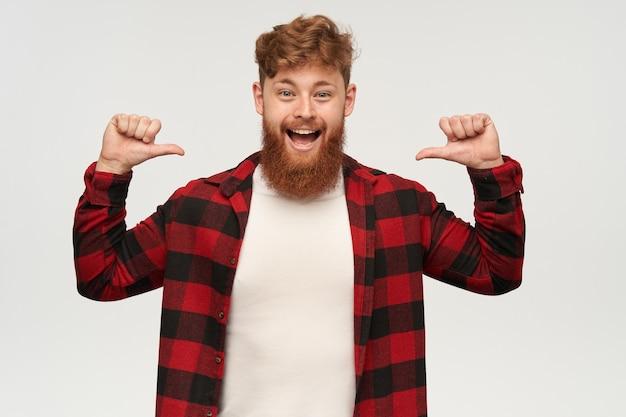 Binnenopname van jonge gelukkige man met grote baard en gemberhaar, draagt modieus shirt, wijst met duim naar zichzelf