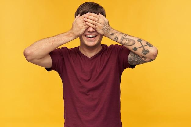 Binnenopname van jonge man draagt rood t-shirt, glimlacht breed en sloot zijn ogen met armen terwijl hij op cadeau wacht