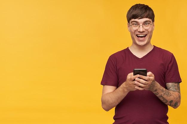 Binnenopname van jonge mannelijke student, glimlacht breed tijdens het lezen van goed nieuws, draagt een rood t-shirt en houdt zijn telefoon in handen