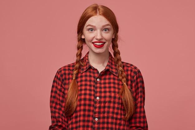 Binnenopname van jonge positieve gembervrouw, glimlacht breed met positieve gezichtsuitdrukking. geïsoleerd over roze achtergrond