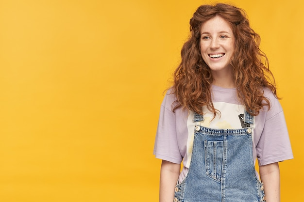 Binnenopname van jonge positieve vrouw, draagt blauwe denim overall en paars t-shirt, voelt zich gelukkig en tevreden, kijkt opzij met positieve gezichtsuitdrukking