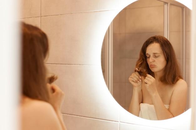 Binnenopname van jonge volwassen vrouw die beschadigd haar vindt, voor een spiegel in de spiegel staat, kijkend naar droge haarpunten, gezondheidszorg, behandelingsprocedures.