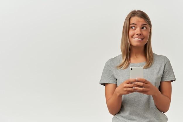 Binnenopname van jonge volwassen vrouw, draagt grijs t-shirt, sms't met haar vriendje, kijkt opzij en bijt op haar lip, glimlacht breed op wit