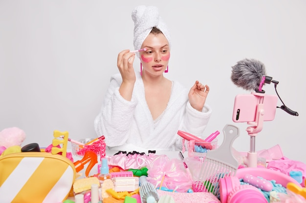 Binnenopname van jonge vrouwelijke modelfilms make-up instructievideo past oogschaduw toe en roze schoonheidspatches onder de ogen geeft online gezichtsklassen