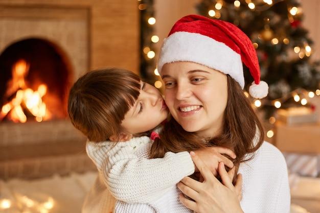 Binnenopname van moeder en haar dochtertje die elkaar omhelzen, een goed humeur hebben, een klein schattig meisje dat haar mama kust, vrolijk kerstfeest en gelukkig nieuwjaar.