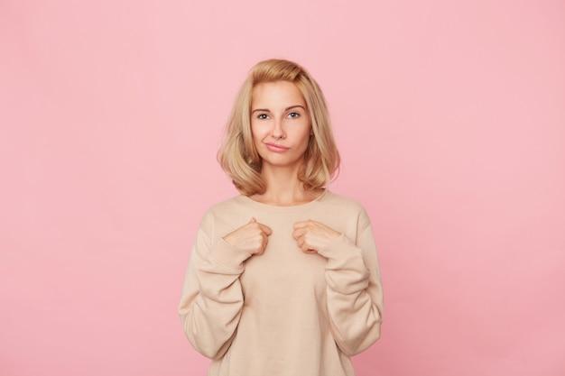 Binnenopname van mooie jonge vrouw voelt zich gelukkig, houdt haar handen op haar borst roze