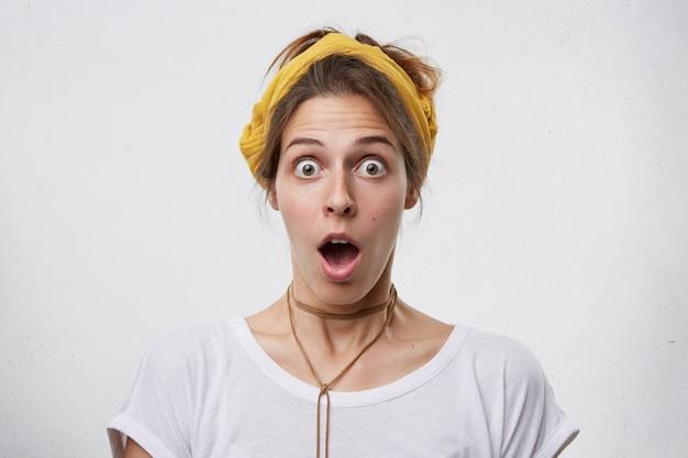 Binnenopname van mooie vrouw die kijkt met afgeluisterde ogen en open mond met een gele sjaal op het hoofd, een hanger en een wit casual t-shirt met een verbaasde uitdrukking