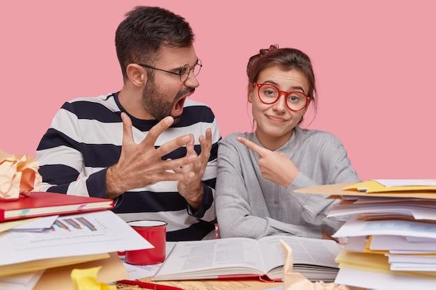 Binnenopname van mooie vrouw wijst naar boze vriend, geeft hem de schuld van een mislukking, samen studeren, voorbereiden op de eindtest op de universiteit, leerboek lezen, poseren in de coworking-ruimte