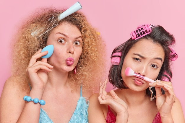 Binnenopname van multi-etnische jonge vrouwen die make-up doen met cosmetische borstel