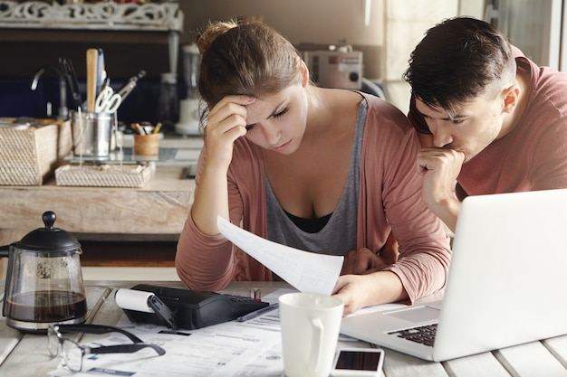 Binnenopname van ongelukkig jong gezin dat zich zorgen maakt over financiële problemen en oplopende rekeningen, document met gefrustreerde blikken leest terwijl ze samen de binnenlandse financiën in hun keuken berekent
