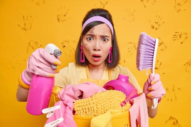 Binnenopname van ontevreden aziatische vrouw die bezig is met seizoensgebonden huishoudelijke klusjes gebruikt wasmiddel voor het wassen van ramen reinigt meubels met borstel doet wasgoed heeft vuil gezicht draagt rubberen handschoenen met hoofdband