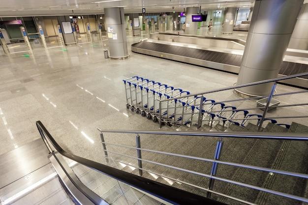 Binnenopname van roltrap en bagageclaim bij terminal