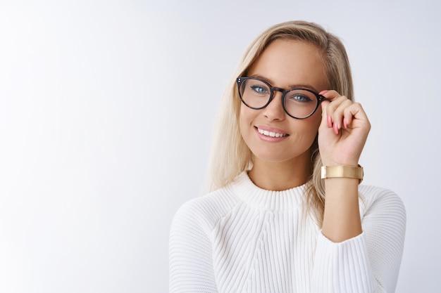 Binnenopname van slimme en succesvolle vrouwelijke ondernemer die manieren deelt om succes aan te raken en frames aan te raken die een bril controleren die opgetogen en volbracht glimlacht terwijl ze zelfverzekerd naar de camera kijkt tegen de witte muur.
