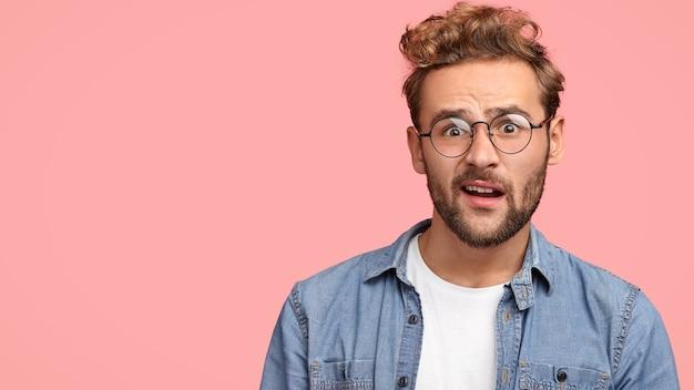 Binnenopname van verbaasde gefrustreerde man fronst zijn wenkbrauwen en kijkt verbijsterd, reageert op een plotseling bericht, gekleed in modieuze kleding, geïsoleerd over roze muur