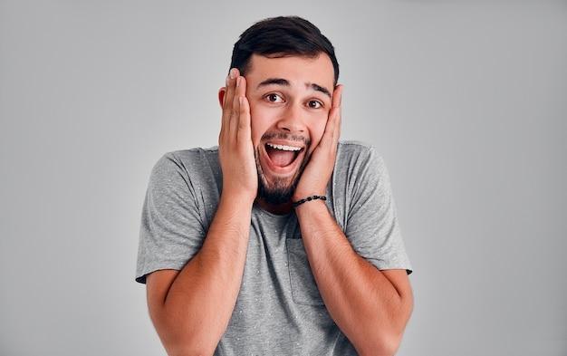 Binnenopname van verbaasde opgewonden man gelooft zijn succes niet, houdt handen op het hoofd, staart naar de camera, zegt omg of wauw aangenaam verrast mannetje verheugt zich op geboorte van kind, wordt gelukkige jonge vader