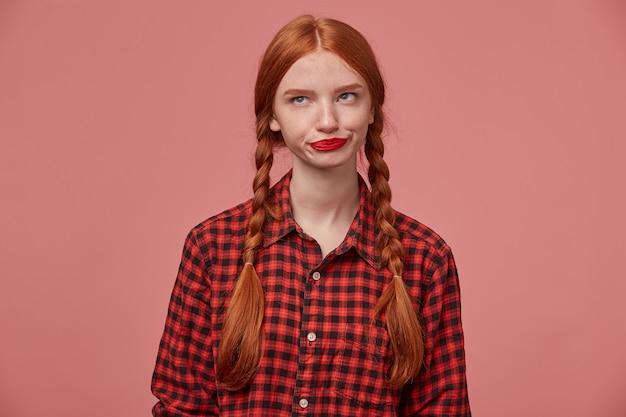 Binnenopname van verdrietig negatief gembervrouwtje, op haar lippen drukkend, kijkt opzij naar kopieerruimte met verwarde gezichtsuitdrukking