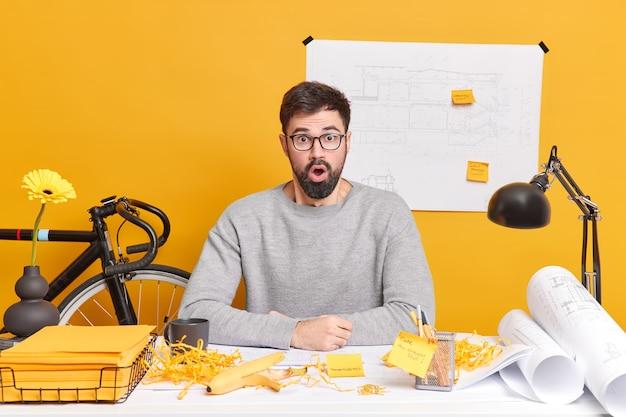 Binnenopname van verraste bebaarde man verbijsterd, poseert op het bureaublad met papieren plaknotities en blauwdrukken in de buurt maakt verslag