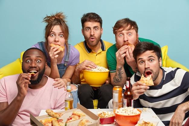 Binnenopname van verraste vrienden van gemengd ras, eet popcorn, pizza, heb angstige paniekerige gezichten, geniet van horrorfilms, heb vrije tijd in het avondweekend, zit op de bank. mensen en vrije tijd concept