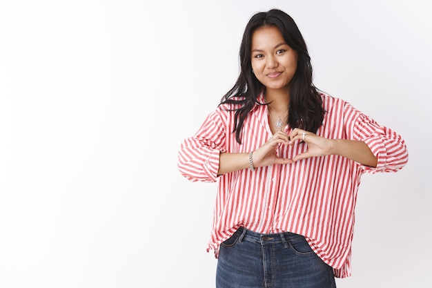 Binnenopname van vriendin in gestreepte blouse met tatoeage die bekent in sympathie met een hartgebaar in de buurt van het lichaam en schattig lacht naar de camera, liefde en romantische gevoelens deelt. relatie concept