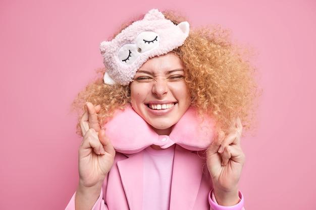 Binnenopname van vrij vrolijke vrouw gelooft in geluk houdt vingers gekruist glimlacht positief hoopt dat droom uitkomt maakt wens voor het slapen slapen draagt slaapartikelen geïsoleerd over roze muur.