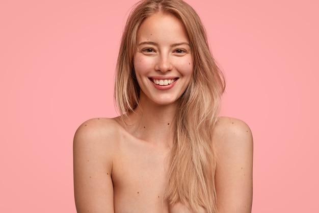 Binnenopname van vrolijke blanke vrouw met vriendelijke uitdrukking en charmante glimlach, staat half naakt tegen een roze muur, heeft witte, gelijkmatige tanden en een schone, zachte huid. positiviteit concept