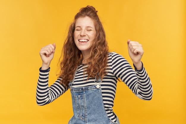 Binnenopname van vrolijke grappige gembervrouw, draagt denim overalls en gestript shirt, dansend terwijl ze naar haar favoriete muziek luistert. geïsoleerd over gele muur
