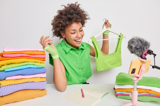 Binnenopname van vrouwelijke online shopper met vrolijke uitdrukking houdt kleding op hanger