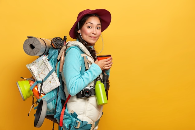 Binnenopname van vrouwelijke reiziger heeft koffiepauze, geniet van reis, draagt rugzak met noodzakelijke dingen en kaart, heeft lange route, draagt hoed en comfortabele kleding