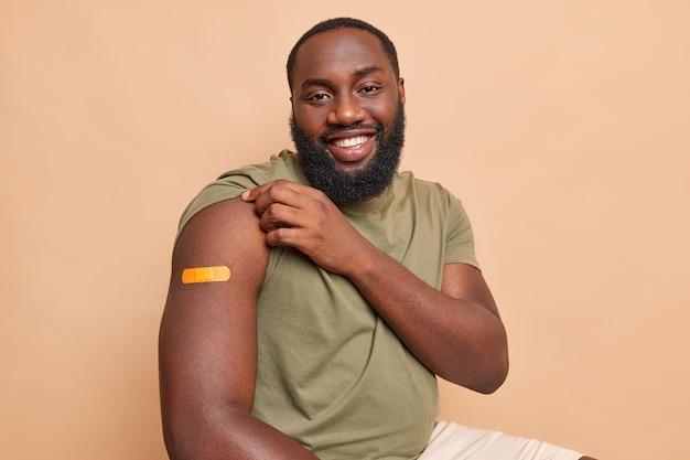 Binnenopname van zwarte afro-amerikaanse volwassen man toont arm met medische pleister krijgt vaccinatie graag gevaccineerd tegen coronavirus geïsoleerd over beige muur