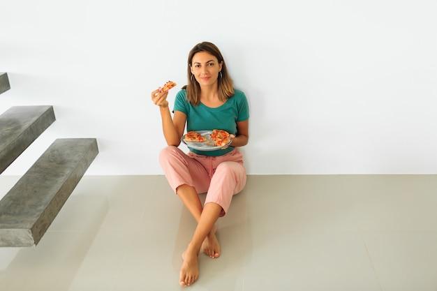Binnenportret die van gelukkige vrouw pizza met kaas eten, die op flor in modern huis zitten