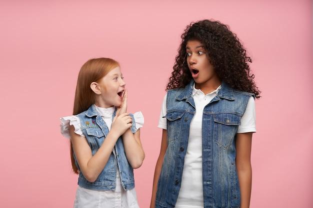 Binnenportret met jong koppel geschokt mooie meisjes die verbaasd naar elkaar kijken met brede mond open en verrast ogen ronddraaien, geïsoleerd op roze