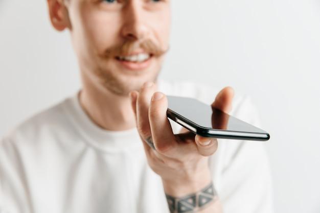 Binnenportret van aantrekkelijke jonge man die op grijze ruimte wordt geïsoleerd, smartphone vasthoudt, stembesturing gebruikt, zich blij en verrast voelt
