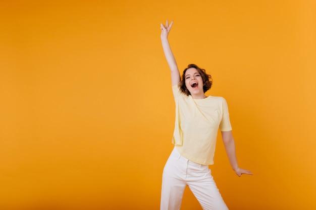 Binnenportret van bleke vrouw met donker haar die met omhoog hand opstaan. verfijnd brunette meisje in geel t-shirt ontspannen tijdens fotoshoot op lichte muur.