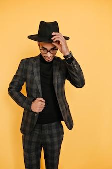 Binnenportret van blij afrikaans mannelijk model dat speels op gele muur stelt. zelfverzekerde zwarte jongeman in jas zijn hoed aan te raken tijdens fotoshoot.