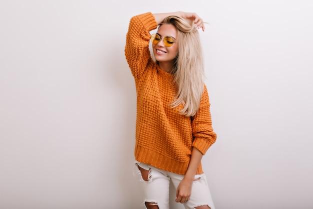 Binnenportret van blije blonde vrouw die gescheurde spijkerbroek en ronde gele bril draagt