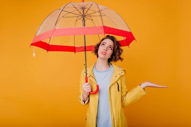 Binnenportret van boos jong vrouwelijk model in de herfstregenjas. foto van droevige krullende dame die zich onder trendy paraplu bevindt en omhoog kijkt.