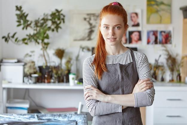 Binnenportret van charmante zelfverzekerde jonge roodharige ambachtenvrouw die een grijze schort draagt die zich in haar atelier bevindt, haar handen gekruist houdt en glimlacht, klaar voor het proces van creatie en hard werken