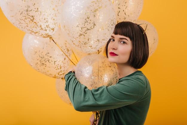 Binnenportret van donkerbruin geïsoleerd feestvarken met kort haar. aantrekkelijk vrouwelijk model poseren met feestballonnen.