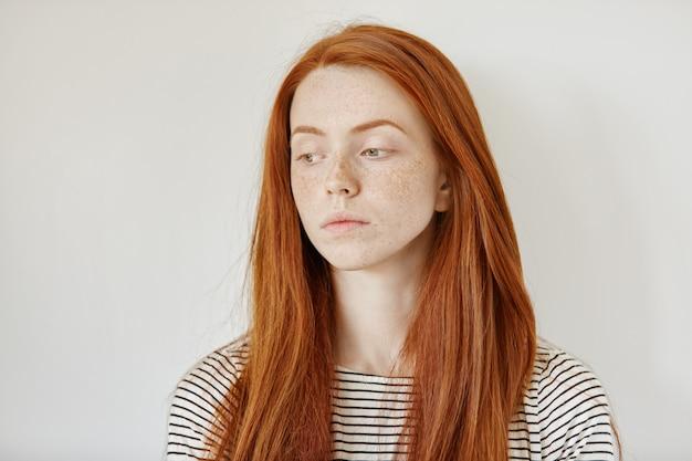 Binnenportret van droevige jonge vrouw die haar lang gemberhaar los het kijken neer met ongelukkige gezichtsuitdrukking dragen
