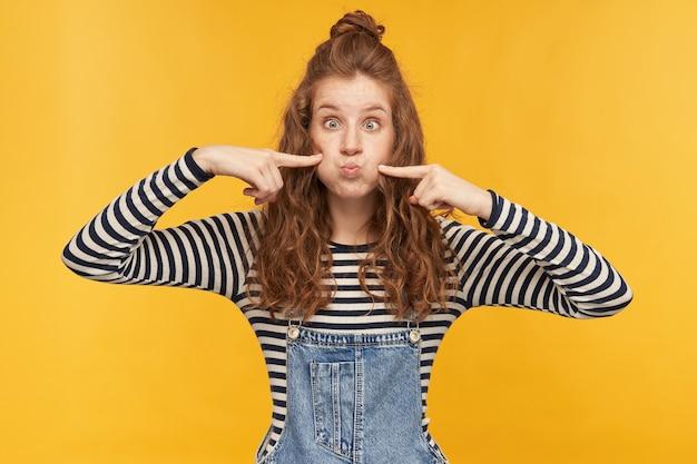 Binnenportret van een jonge, grappige vrouw, die een grapje maakt en haar wangen opblaast, ze aanraakt met een vingers, houdt de ogen wijd open tijdens het spelen met haar kinderen. geïsoleerd over gele muur